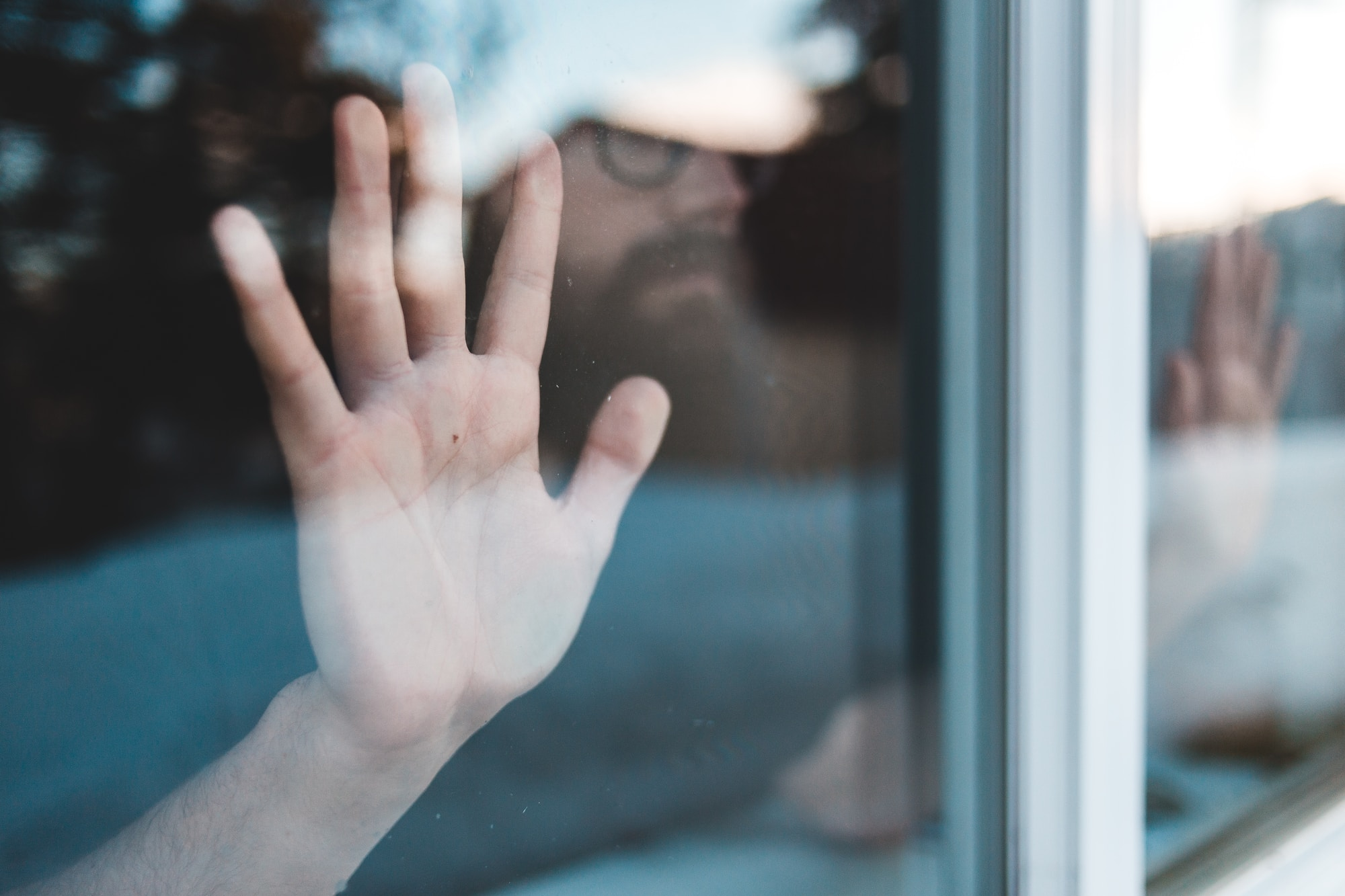 persons hand on glass window