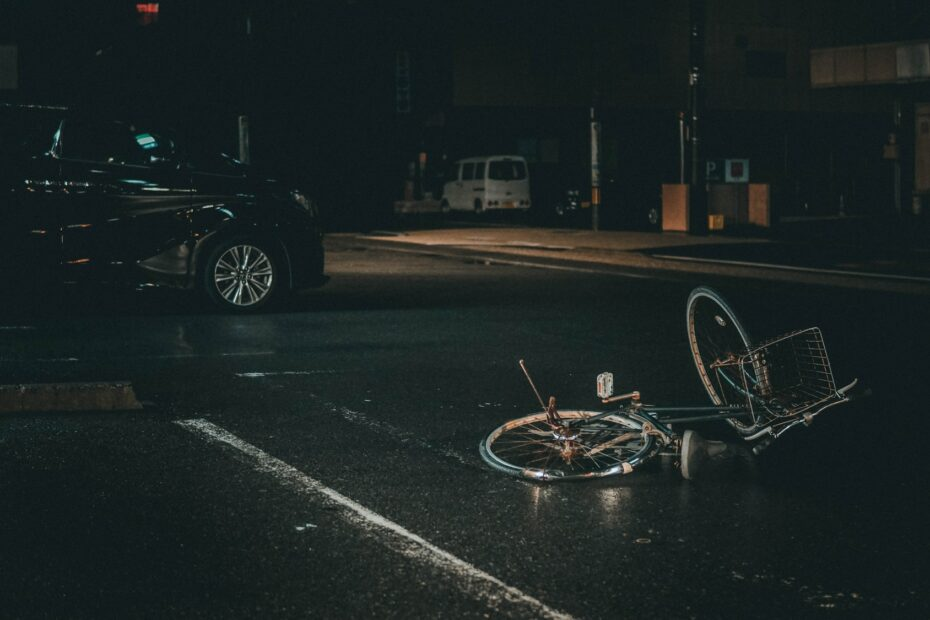 grey bicycle on road near black vehicle at nighttime