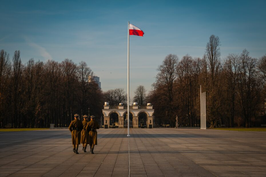 three military soldiers walking at the park near flag pole