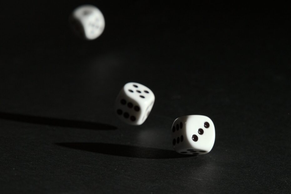 3 white dice on black surface